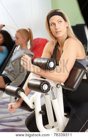 Pretty young blond girl doing workout at the gym on weight machine.