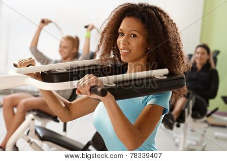 Pretty ethnic girl exercising on weight machine at the gym, smiling.
