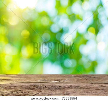 Old wooden table with green foliage on the background.
