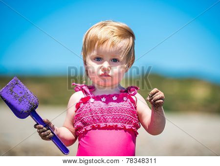 little cute girl close-up playing in the sand with a shovel on the beach on a beautiful summer day