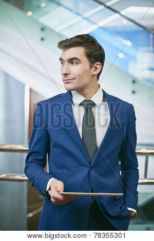 Young businessman with digital tablet looking aside