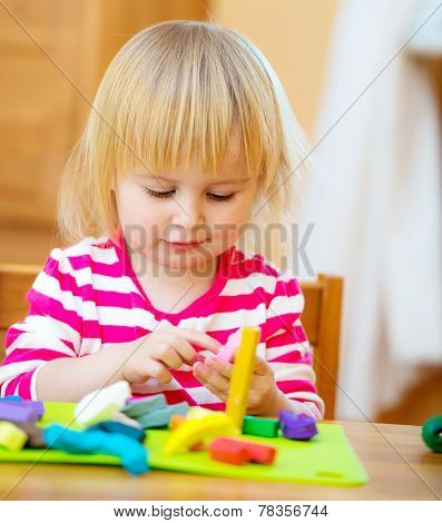Smiling girl playing with plasticine at home