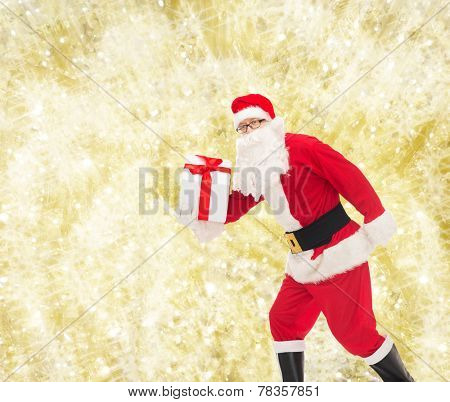 christmas, holidays and people concept - man in costume of santa claus running with gift box over yellow lights background