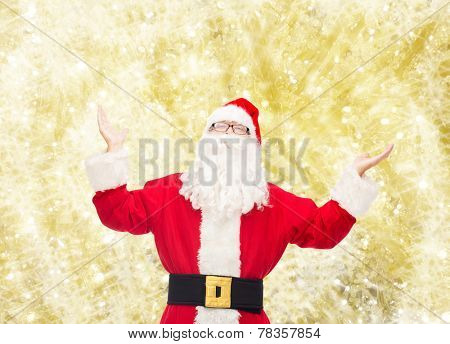 christmas, holidays and people concept - man in costume of santa claus with raised hands over yellow lights background