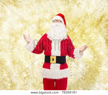 christmas, holidays and people concept - man in costume of santa claus over yellow lights background