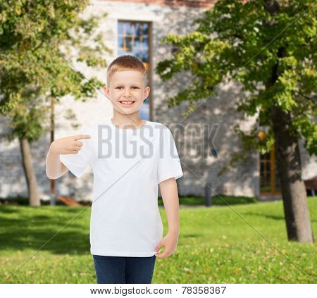 advertising, gesture, people and childhood concept - smiling boy in white blank t-shirt pointing finger at himself over campus background