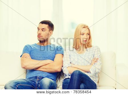 love, family and happiness concept - unhappy couple not speaking after having argument at home