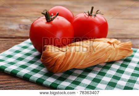 Smoked braided cheese on wooden table