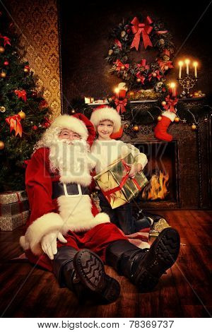 Portrait of Santa Claus with a boy sitting at home decorated for Christmas. Christmas scene.