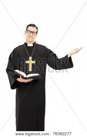 Vertical shot of a peaceful young priest holding a bible isolated on white background