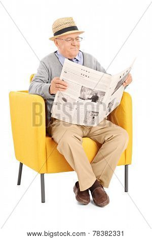 Vertical shot of a senior reading a newspaper in a modern armchair isolated on white background