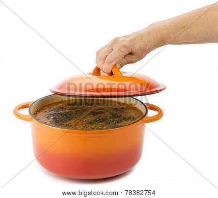 Female hand opens lid of lentil soup in cast iron cooking pot isolated on white background.