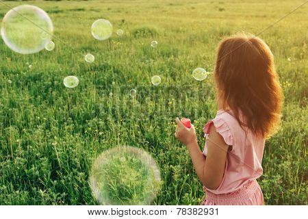 Girl In Pink Dress Blowing Soap Bubbles In Summer