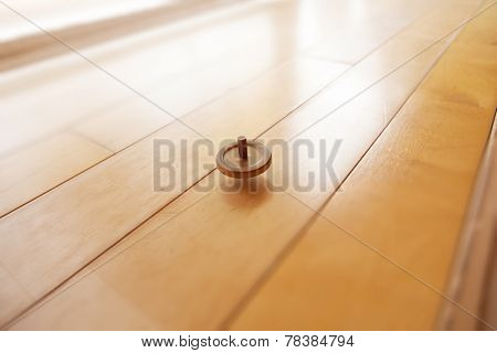 Spinning top on wooden flooring