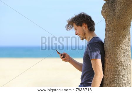 Side View Of An Attractive Man Using A Smart Phone On The Beach