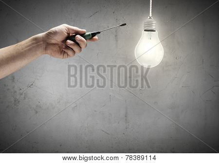 Close up of screwdriver in hand and light bulb