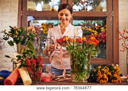 Pretty florist making bouquets of fresh flowers and decorating them in shop