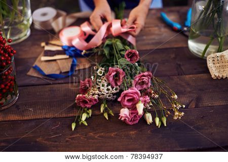 Hands of decorator tying bunch of flowers up with pink ribbon