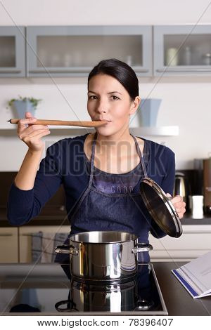 Young Housewife Tasting Her Cooking