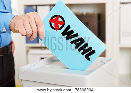 Hand with ballot paper on ballot box during election