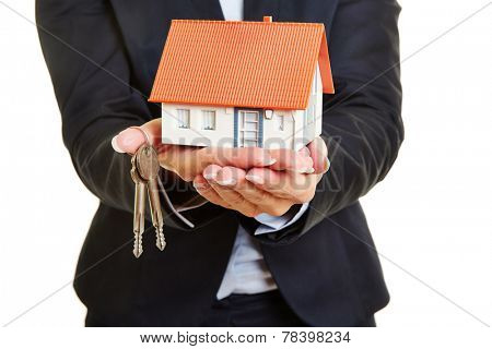 Hands of a female real estate broker holding a small house and keys