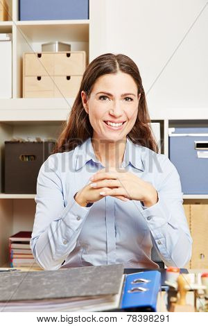 Smiling woman sitting at her desk in an office
