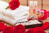 foto of swedish sauna  - roses rose petals rose extract bottles bathing salt and a towel - JPG