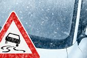 stock photo of ice-scraper  - Snow on an ice covered windshield with warning sign - JPG