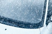 image of ice-scraper  - Snow on an ice covered windshield with copy space - JPG