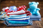 picture of bodysuit  - Baby clothes stack on a wooden table - JPG