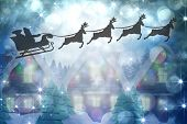 stock photo of quaint  - Silhouette of santa claus and reindeer against quaint town with bright moon - JPG