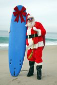 foto of blue things  - Santa Claus stands on the beach by the Ocean holding a Blue Surfboard with a Large Red Bow on it as a Christmas Gift to some lucky Boy or Girl - JPG
