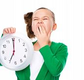 picture of hush  - Cute girl is holding big clock and showing hush gesture isolated over white - JPG