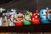 pic of teapot  - Close up Row of colorful teapot on shelf - JPG