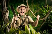 picture of machete  - Cheerful adventurer with machete and fists raised in the jungle - JPG