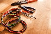 pic of wire cutter  - Colored cables or wires and a wire cutter tools on a wooden work desk - JPG