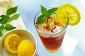 stock photo of iced-tea  - tall glass of iced tea with lemon and fresh mint - JPG