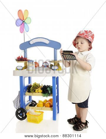 An adorable preschooler standing by his fruit stand while calculating his profits to show the viewer.  The stand's signs are left blank for your text.  On a white background.