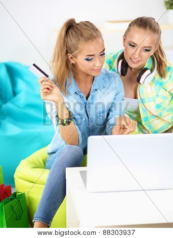 Two young women sitting with laptop and credit cart at home.