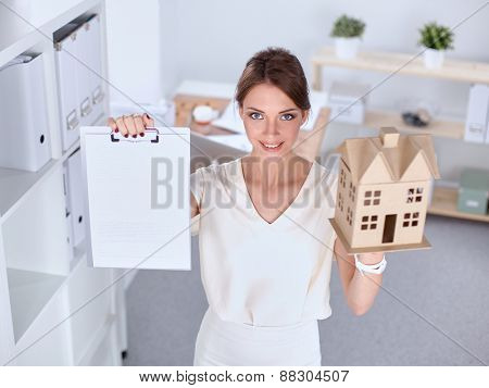 Portrait of female architect holding a little house, standing in office .