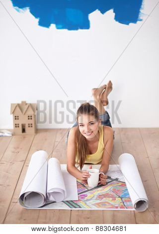 Young woman lying on the floor and looking at blueprint