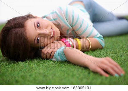 Beautiful young woman lying on green grass .