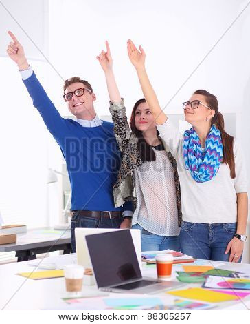 Young business people standing at office near desk and pointing up.