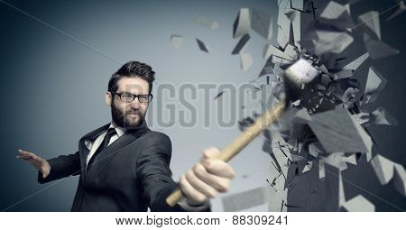 Young businessman hitting concrete wall with a hammer