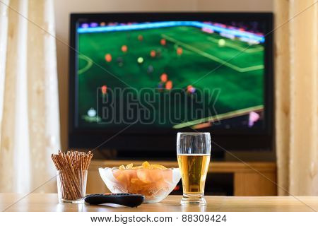 Television, Tv Watching (football, Soccer Match) With Snacks Lying On Table