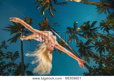 Young attractive woman in swimsuit flying in the air on sky and palm trees background