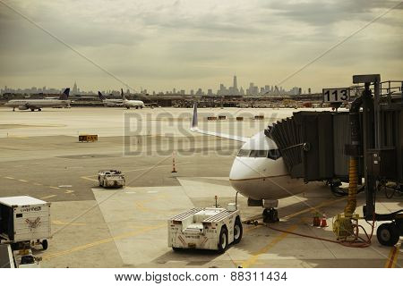 NEWARK, NJ - MAY 11: Airplane at airport with New York City skyline on May 11, 2014 in Newark, New Jersey. Newark airport is 10th busiest in US