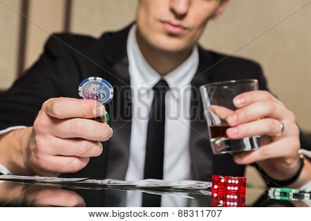 . Young guy in the casino at the gaming table.