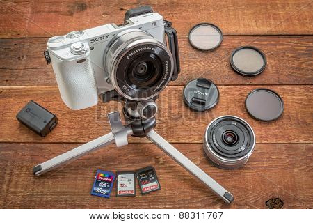 FORT COLLINS, CO, USA, April 17,  2015:  Sony A6000 mirrorless digital camera on a table tripod surrounded by a set of filters, memory cards, lens cap, battery and lens  on a grunge barn wood table.