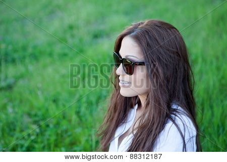 Brunette cool girl with brackets and sunglasses in the park